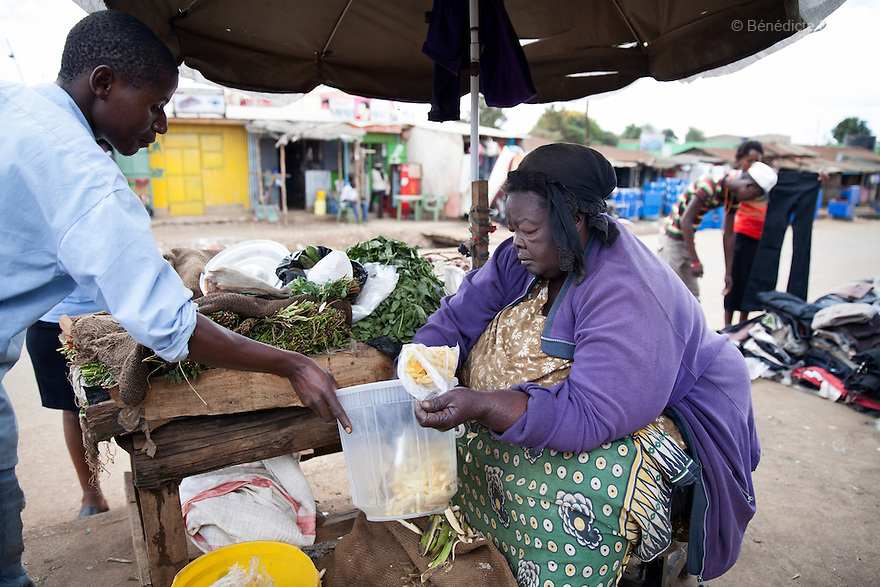 """""""Mama Safi"""" sells vegetables and fried potatoes in the street in front of her home inKawangware slum in Nairobi, Kenya on March 22, 2013. Susan Kalai aka """"Mama Safi"""" is a 53 year old Kenyan woman with severe morbid obesity living inKawangware slum in Nairobi, Kenya. Shelives on less than $1 USD a day, selling vegetables and fried potatoes in the street in front of her house. She has 7 children, the youngest one is 9 yearsold. She suffersfrom several obesity-related diseases. She can't walk, has a lot of pain in her legs and back and also has difficulties to breathe. She says """"I was born big. I was always like this.Both my parents and my sister are big too. So for me it's normal. Nothing is wrong with me"""".She has no knowledgeabout obesity and she can't go to the doctor to get treated because she has no money to pay for it. She is afraid to die of a heart attack. Although large parts of Africa areplaguedwith malnutrition, the continent must now also deal with another problem:obesity.Obesity is fast becoming a serious problem in Kenya and even the poorest are now being affected. Obesity rates are climbing around the world and they are rising faster in developing countries than in developed ones. (Photo by Benedicte Desrus)"""
