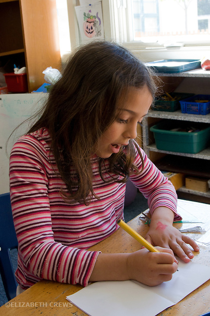 Berkeley CA, Kindergarten student sounding out words while writing in her composition book