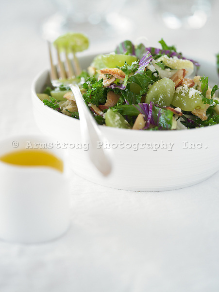 Kale salad with grapes in white bowl with dressing on the side