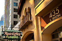 The neon Ratcliffe's Flower sign still hangs outside the Mediterranean Revival Style Ratcliffe Flowers building, a Charlotte landmark located in downtown Charlotte, NC. Built in the 1920s, the building that originally housed a florist shop became a restaurant (Carpe Diem) in the 1990s. When the building was transformed into the midrise Ratcliffe Condos in 2002, the shop was moved during construction and then replaced in its original position. The residential and retail building was then constructed around the original Ratcliffe's shop. Today, the former flower shop is home to Ratcliffe On The Green, a restaurant of French-influence cuisine. The Ratcliffe Condos sit on The Green, an uptown Charlotte Center City project that includes an underground parking deck with a passive park on top. The Green park includes fountains, landscaped walkways, motion-activitated stone walls, chess boards built into stone tables and riddles on the ground.