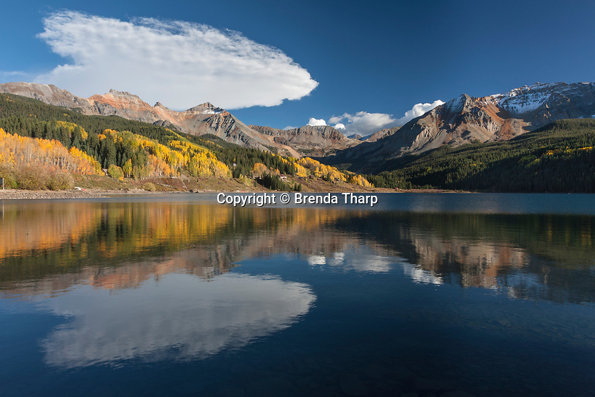 Clouds and golden aspen trees reflect in the waters of Trout Lake, Colorado.