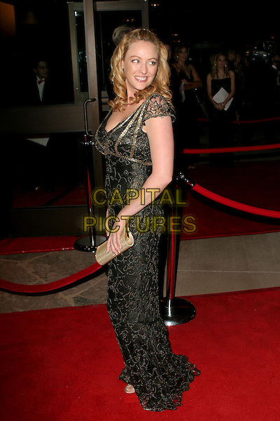 VIRGINIA MADSEN.17th Annual Palm Springs International Film Festival Gala Awards Presentation - Arrivals held at the Palm Springs Convention Center, Palm Springs, California.  .January 7th, 2006.Photo: Zach Lipp/AdMedia/Capital Pictures.Ref: ZL/ADM.full length black gold detail dress clutch purse looking over shoulder.www.capitalpictures.com.sales@capitalpictures.com.© Capital Pictures.