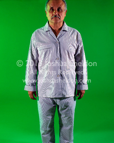 Old man in pajamas on green background