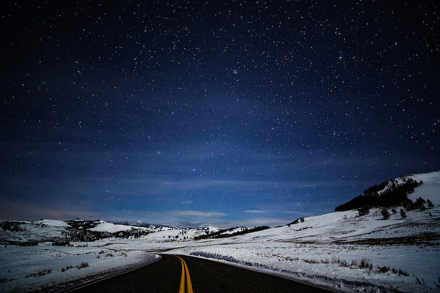 The road trails off into the distance with bright stars overhead at night in Yellowstone National Park, Wyoming.
