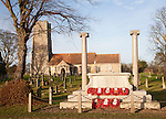 War memorial with poppy wreaths at St John the Baptists church, Snape, Suffolk, England