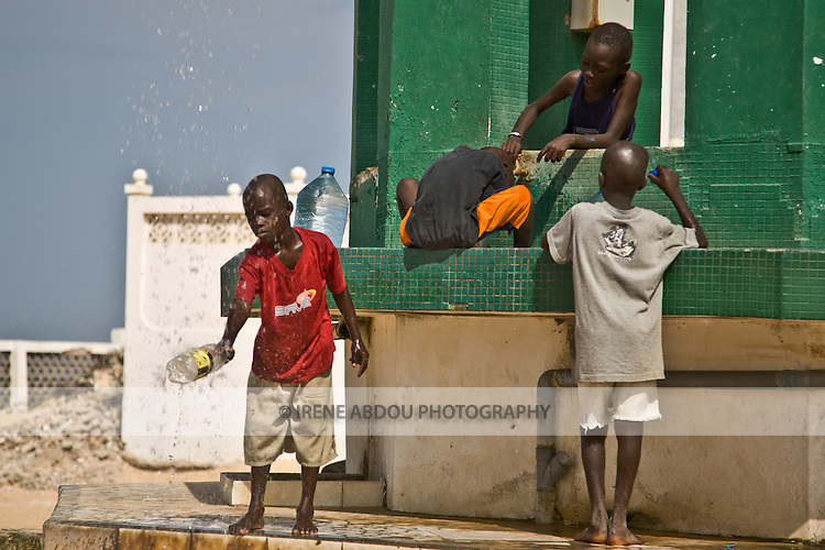 "Children wash at the well of Diamalaye (zem-zem holy water) in front of the Seydina Limamou Laye Mausoleum, which sits on the coast of Senegal in the fishing village of Yoff.  Seydina Limamou Laye (1843-1909) was the founder of the Layène (meaning ""partisans of God"") brotherhood."