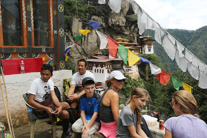 A family of Australian tourists picnic overlooking the Tiger's Nest Buddhist temple perched high up, and almost inaccessible except for a steep 3 hour climb, Paro, Bhutan..Bhutan the country that prides itself on the development of 'Gross National Happiness' rather than GNP. This attitude pervades education, government, proclamations by royalty and politicians alike, and in the daily life of Bhutanese people. Strong adherence and respect for a royal family and Buddhism, mean the people generally follow what they are told and taught. There are of course contradictions between the modern and tradional world more often seen in urban rather than rural contexts. Phallic images of huge penises adorn the traditional homes, surrounded by animal spirits; Gross National Penis. Slow development, and fending off the modern world, television only introduced ten years ago, the lack of intrusive tourism, as tourists need to pay a daily minimum entry of $250, ecotourism for the rich, leaves a relatively unworldly populace, but with very high literacy, good health service and payments to peasants to not kill wild animals, or misuse forest, enables sustainable development and protects the country's natural heritage. Whilst various hydro-electric schemes, cash crops including apples, pull in import revenue, and Bhutan is helped with aid from the international community. Its population is only a meagre 700,000. Indian and Nepalese workers carry out the menial road and construction work.