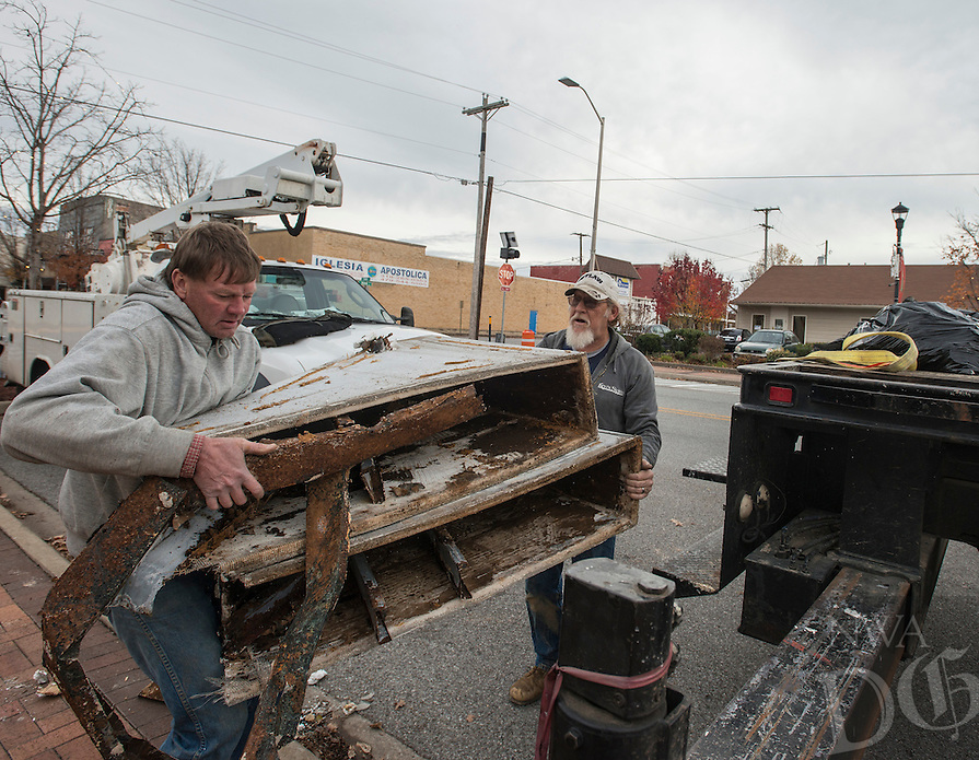 NWA Democrat-Gazette/ANTHONY REYES @NWATONYR<br /> Terry Cloud, left, and Lew Indorf, both with Ken's Signs, load the rusted remains of a monument sign Monday, Dec. 5, 2016 outside the Springdale Chamber of Commerce in downtown Springdale. The crew installed a new base for a new sign that should be installed today (Tuesday).