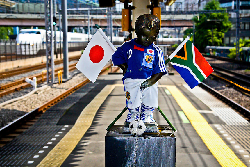 Hamamatsucho station`s wee boy statue dressed in the Japan teams colors to celebrate the South African World Cup soccer Tournament in 2010 with a Shinkansen Bullet train in the background.He is dressed by local ladies depending on seasons & events.