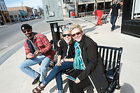 Corinne from Artopia Art Gallery with friends sitting on a  Christina Street bench