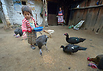 Three-year old Nyda Diaz Vasquez feeds poultry at her home in Tuixcajchis, a small Mam-speaking Maya village in Comitancillo, Guatemala. Her mother, Audelina Vasquez Lopez, watches in the background