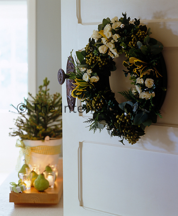 A wreath of white flowers, foliage and berries graces the open door to the living room