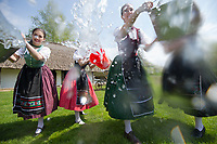 Girls wearing traditional clothes splashes a buckets of water as part of the fertility traditions during the Easter watering celebration in the Skansen open air ethnographic museum in Szenna (about 200 km South-West of capital city Budapest), Hungary on April 14, 2017. ATTILA VOLGYI