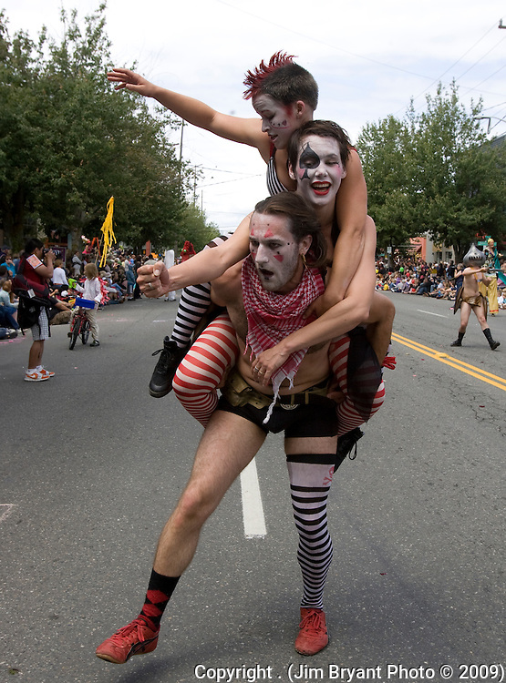 Henry Scott carries Julie Adams (C) and Kristen Ducey during the 21st  Annual Fremont Summer Solstice Parade in Seattle on June 21, 2009.  The parade was held Saturday, bringing out painted and naked bicyclists, bands, belly dancers and floats. (Jim Bryant Photo © 2009)