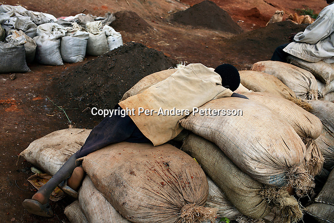 LUBUMBASHI, DEMOCRATIC REPUBLIC OF CONGO - DECEMBER 13: A young boy sleep on bags of cobalt after a long day?s work on December 13, 2005 in Ruashi mine about 20 kilometers outside Lubumbashi, Congo, DRC. About 4,000 young men and children work here, mining copper and cobalt. Some children as young as eight work in the mine under dangerous conditions. Every month a few of the miners are killed. Congo has one of the largest Copper deposits in the world and most of it is exported to China. It?s fueling the thirst for minerals for China?s economic boom. The young men who works in the mine makes a few US dollars a day, and the children much less. The mine is about one hundred years old and has been a source of wealth for the Katanga province for many years. In recent years many foreign companies and shady business people has moved into Congo to plunder its wealth. The country has no elected government and the corruption is rife. Border and customs officials are easily bribed. Congo has had a civil war since 1997 and it?s estimated that nearly 4 million people has died in fighting and because of lack of health care. (Photo: Per-Anders Pettersson/Getty Images)