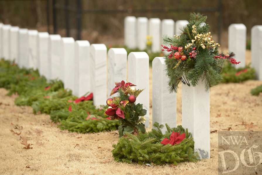 NWA Democrat-Gazette/BEN GOFF @NWABENGOFF<br /> Wreaths decorate grave markers on Saturday Dec. 12, 2015 during the Wreaths Across America ceremony at Fayetteville National Cemetery. Family members and volunteers with various veterans and community groups helped place a balsam remembrance wreath on the grave of each veteran at the cemetery as part of National Wreaths Across America Day.