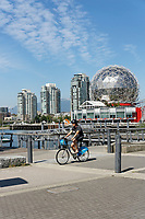 Man riding Mobi bike sharing bicycle with TELUS World of Science dome in back at the Village on False Creek, Vancouver, British Columbia, Canada