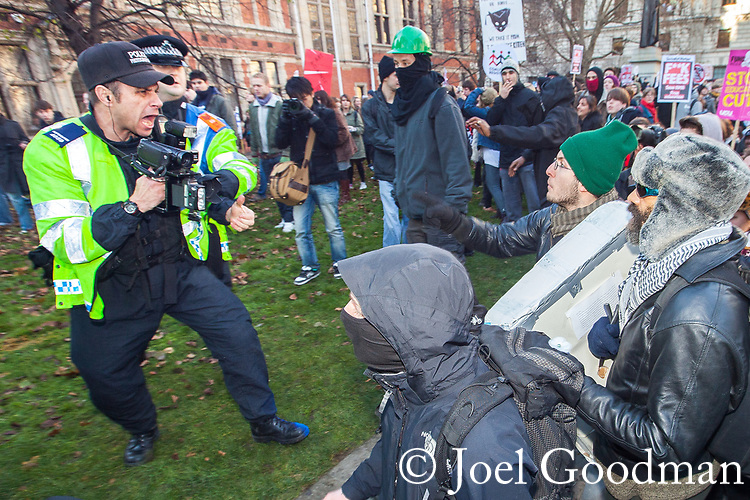 © Joel Goodman - 07973 332324 . 09/12/2010 . London , UK . Students and their supporters clash with an evidence gathering police officer during a demonstration in Parliament Square in London against government cuts to student support , Educational Maintenance Allowance ( EMA ) and rising university tuition fees . Photo credit : Joel Goodman