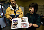 Mitsuo Sugawara and his wife Tomoko pose with photos showing the destruction to their property following the March 11 disasters  on their farm in Higashi-Matsushima, Miyagi Prefecture, Japan on 30 Nov. 2011.Photographer: Robert Gilhooly