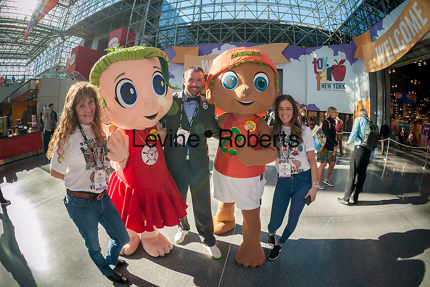 Cathy Arone, left, with her son Brien Arone, center, and her daughter Tessa Davis, left, of SeaBabies with Sandy Dollar and Finley characters promoting their line of environmental products at the 114th North American International Toy Fair in the Jacob Javits Convention center in New York on Sunday, February 19, 2017.  The company is a family business and is committed to teaching children the importance of caring for the planet and also supports 1% For the Planet. (© Richard B. Levine)