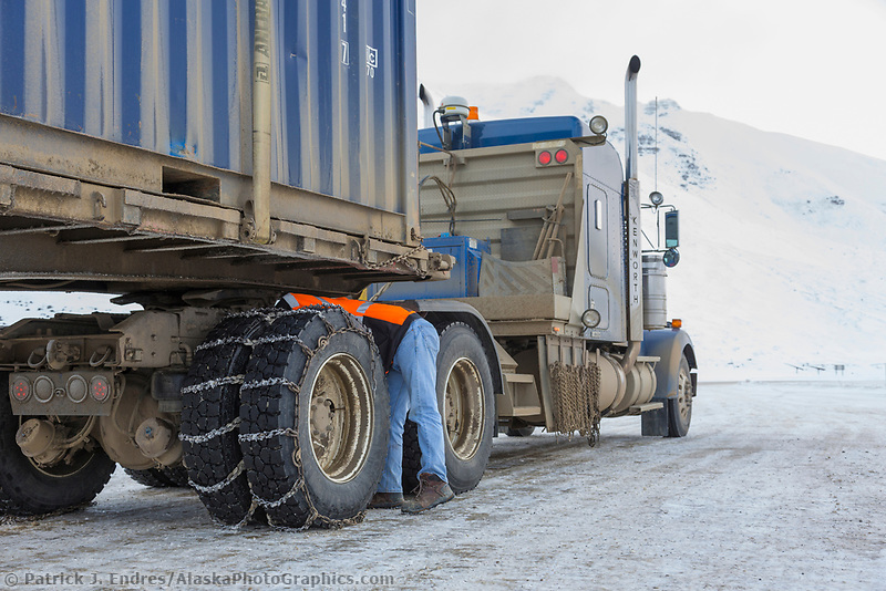 Truck driver puts chains on the truck tires for better traction crossing the atigun pass of the Brooks Range, Arctic, Alaska.