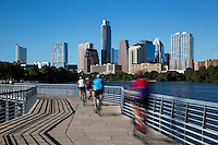 A group of cyclists ride down the Boardwalk Trail which offers stunning views of the Austin cityscape skyline.