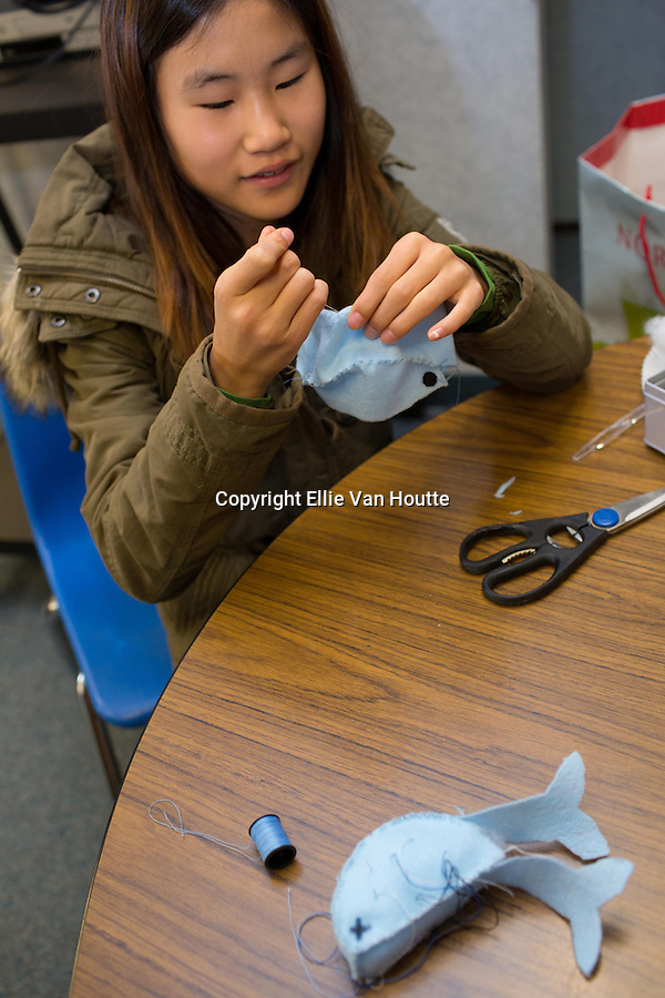 During a break from business, Rachel Lu crafts narwhales for purchase.