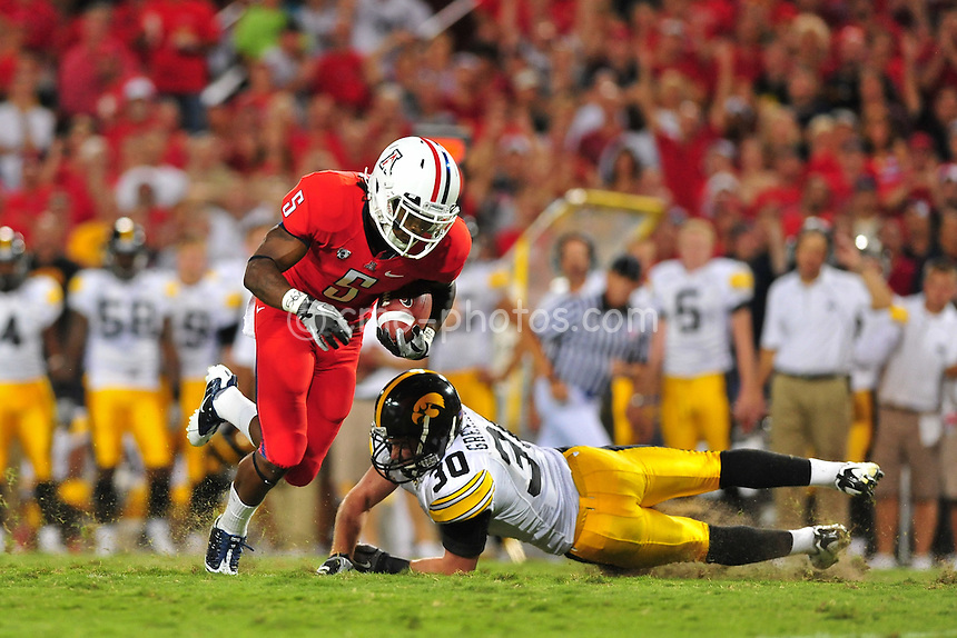 Sept 18, 2010; Tucson, AZ, USA; Iowa Hawkeyes cornerback Brett Greenwood (30) dives after the feet of Arizona Wildcats running back Nic Grigsby (5) in the 2nd quarter of a game at Arizona Stadium.  Arizona won the game 34-27.