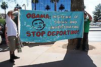 Phoenix, Arizona. June 25, 2012 - Two protesters stand in front of the U.S. Immigration and Customs Enforcement (ICE) building in Phoenix, Arizona to show their opposition to President Obama's deportation policies. Immigrant rights groups protested the United States Supreme Court ruling on Arizona law for upholding SB 1070's provision that will allow police to demand papers if there's reasonable suspicion that a person may be illegally in the country. Photo by Eduardo Barraza © 2012