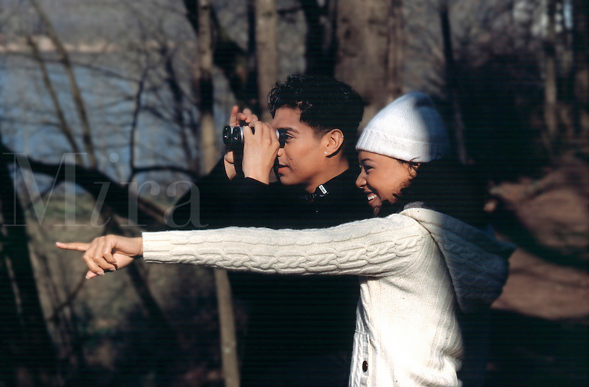 Yound couple woman pointing, man looking through binoculars..MR