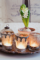 Lit candles in glass patinated cups edged with metal, a Christmas bauble and a potted Hyacinth create a feature in the centre of the living room