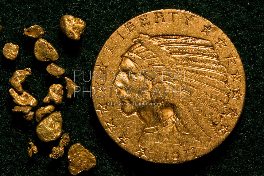 GOLD<br /> Indian Head Gold Coin with Gold Flakes<br /> Elemental gold coin with 99.99 assay on weight, numbered. A highly sought after precious metal, gold is dense, soft, shiny and the most malleable and ductile pure metal known.