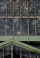 Tropical Rainforest Glasshouse (formerly Le Jardin d'Hiver or Winter Gardens), 1936, René Berger, Jardin des Plantes, Museum National d'Histoire Naturelle, Paris, France. Detail of windows of the glass and metal structure showing the luxuriant foliage within. To the bottom of the picture is the roof of the Desert and arid lands glasshouse.