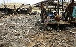 A Cyclone Nargis survivor cocks at wat is left of her home, in Irrawaddy Division, May 10, 2008. Despairing survivors in Myanmar awaited emergency relief on Friday, a week after 100,000 people were feared killed as the cyclone roared across the farms and villages of the low-lying Irrawaddy delta region. The storm is the most devastating one to hit Asia since 1991, when 143,000 people were killed in neighboring Bangladesh. Photo by Eyal Warshavsky  *** Local Caption *** ëì äæëåéåú ùîåøåú ìàéì åøùáñ÷é àéï ìòùåú áúîåðåú ùéîåù ììà àéùåø