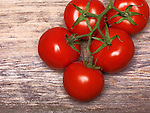 Red tomatoes on rustic wooden background