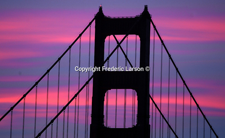 The morning sunrise looking through San Francisco Golden Gate Bridge lite up the skies in array of different hues looking eastward from the Sausalito, California.