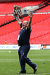 A member of the Grimsby Town back rrom staff holds the Vanarama Conference Playoff trophy aloft after victory in the 2015 Vanarama Conference Promotion Final match between Grimsby Town and Bristol Rovers at Wembley Stadium, London<br /> Picture by David Horn/eXtreme aperture photography +44 7545 970036<br /> 17/05/2015