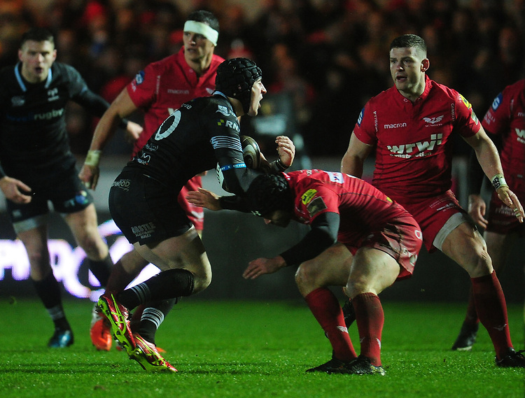 Ospreys' Sam Davies is tackled by Scarlets' Leigh Halfpenny<br /> <br /> Photographer Kevin Barnes/CameraSport<br /> <br /> Guinness Pro14 Round 11 - Scarlets v Ospreys - Tuesday 26th December 2017 - Parc y Scarlets - Llanelli<br /> <br /> World Copyright &copy; 2017 CameraSport. All rights reserved. 43 Linden Ave. Countesthorpe. Leicester. England. LE8 5PG - Tel: +44 (0) 116 277 4147 - admin@camerasport.com - www.camerasport.com