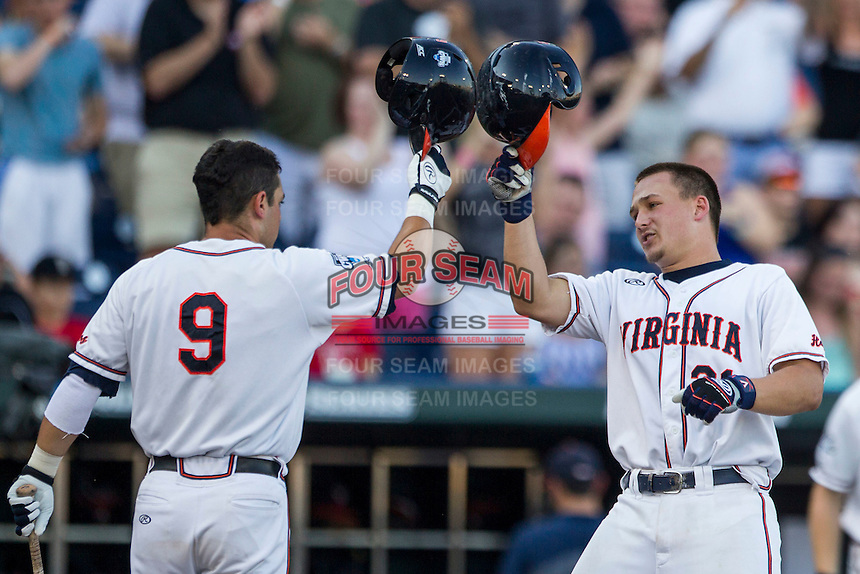 Virginia Cavaliers catcher Matt Thaiss (21) is greeted at the plate by teammate Kenny Towns (9) after his first inning home run against the Florida Gators in Game 13 of the NCAA College World Series on June 20, 2015 at TD Ameritrade Park in Omaha, Nebraska. The Cavaliers beat the Gators 5-4. (Andrew Woolley/Four Seam Images)