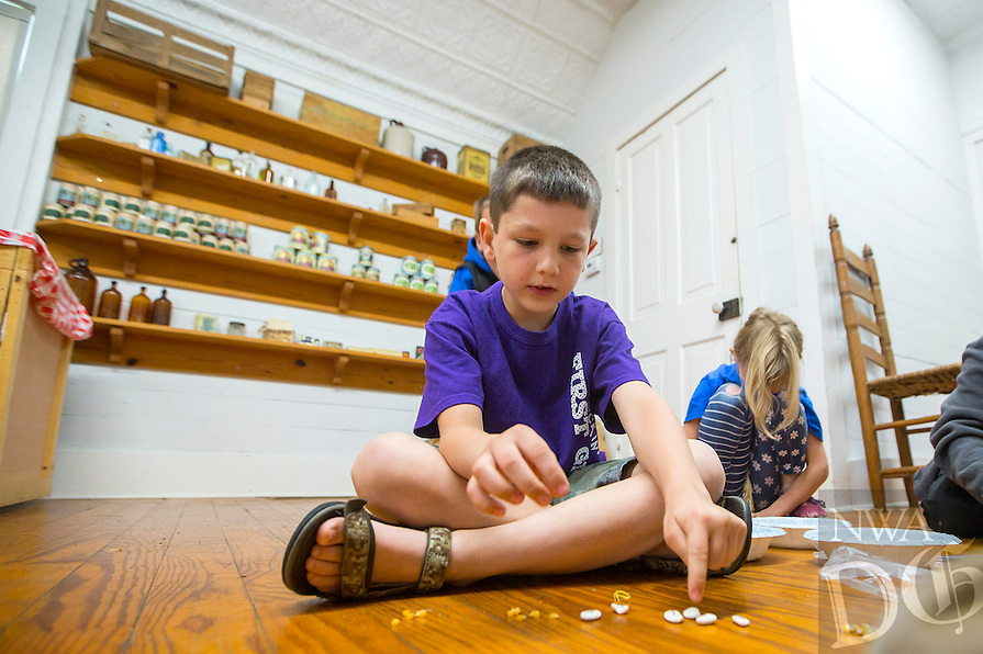 NWA Democrat-Gazette/JASON IVESTER<br /> Owen Friesen, Elm Tree Elementary first-grader, plays a game with beans and corn on Thursday, May 19, 2016, in the general store at the Shiloh Museum of Ozark History in Springdale. The five first-grade classes from the Bentonville school visited the museum as they begin their studies on Arkansas history.