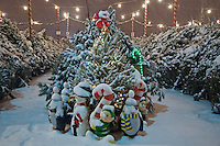 Plastic ornamental characters are covered with fresh snow at the entrance to a  Christmas tree sale lot at a Columbus, Ohio, nursery lot.<br />