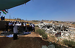 Palestinians pray friday prayer near the remains of the Palestinian buildings was demolished by Israeli security forces, in the the Palestinian village of Sur Baher in East Jerusalem, July 26, 2019. Photo by Ahmed Mezher/ WAFA