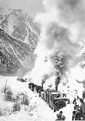 Rotary snowplow train with three engines. There is another train in the near distance with crew cars. A crew of shovelers is breaking up the crust for the rotary.  The letterng on the plow may say D&amp;RG.  If so, it may be #OM judging by the roof lines.<br /> D&amp;RGW  Animas Canyon, CO
