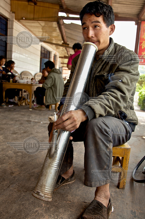 A man smokes a cigarette in a large tin water pipe. /Felix Features