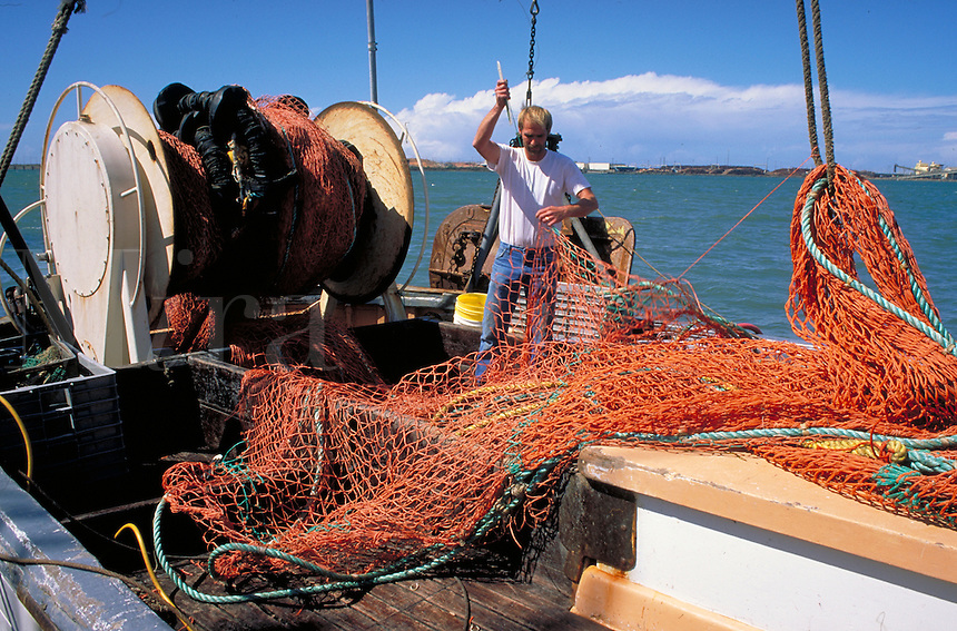 fisherman mending orange fishing nets on board fishing boat. fisherman.