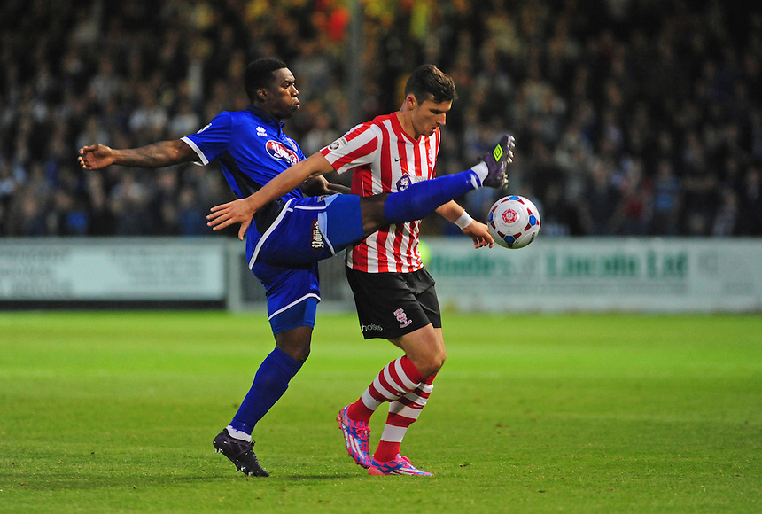 Lincoln City's Sean Newton shields the ball from Grimsby Town's Jon-Paul Pittman<br /> <br /> Photo by Chris Vaughan/CameraSport<br /> <br /> Football - English Football Vanarama Conference Premier League - Lincoln City v Grimsby Town - Tuesdayb9th September 2014 - Sincil Bank - Lincoln<br /> <br /> &copy; CameraSport - 43 Linden Ave. Countesthorpe. Leicester. England. LE8 5PG - Tel: +44 (0) 116 277 4147 - admin@camerasport.com - www.camerasport.com