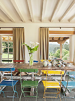 A vase of calla lilies stands on top of the wooden dining table surrounded by colourful folding chairs