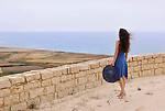 Woman in a blue summer dress standing alone enjoying view on the Mediterranean Sea Cyprus