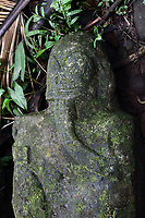 Stone carved female tiki sculpture in grey keetu or volcanic tuff, with finely carved features - a tattooed and pierced right ear, Mata-related motifs on the face, tattooed lips, a crescent moon diadem, and a hand resting under the chin, at Te Fiifii, a religious sanctuary or meae, built by the pre-European Marquesian civilisation, 80m South West of the Iipona archaeological site, near the village of Puamau, on the island of Hiva Oa, in the Marquesas Islands, French Polynesia. This tiki is thought to have originally been part of a facade on the North side of the paepae or platform. Tiki sculptures are usually carved in wood or stone and represent Ti'i, a half-human half-god ancestor who is believed to be the first man. Tiki often have a huge head, symbolising power, and big eyes symbolising knowledge. Tiki are respected and are often placed outside houses as protective statues. Picture by Manuel Cohen
