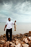 BELIZE. Belize City, a fisherman holds up a Snook that he just caught on the waterfront, Caribbean Sea